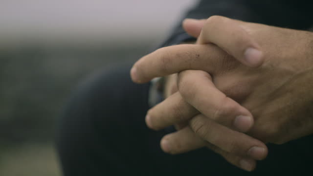 vidéos et rushes de sequence showing the clasped hands of a seated middle-aged man on a beach, uk. - un seul homme