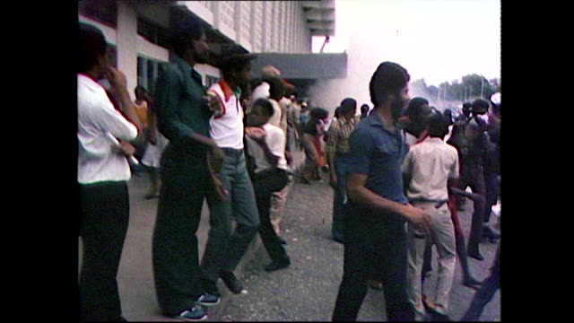 sequence showing the crowds of people waiting to attend bob marley's state funeral running away after tear gas was fired on them by police; 1981. - ボブ・マーリー点の映像素材/bロール