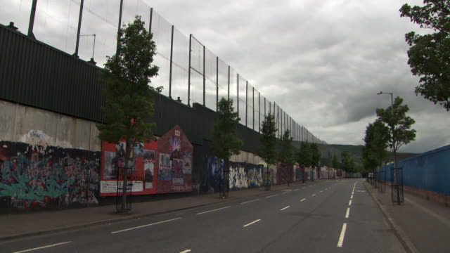 Sequence showing the high walls, fencing and Unionist graffiti of a peace line ('interface') in Belfast, Northern Ireland.