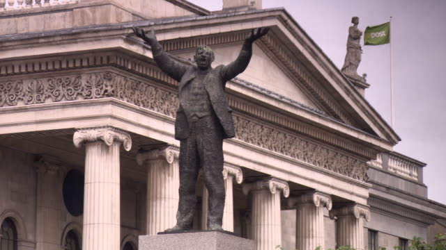 sequence showing the jim larkin monument standing in front of the general post office on o'connell street, dublin, ireland. - 説得点の映像素材/bロール