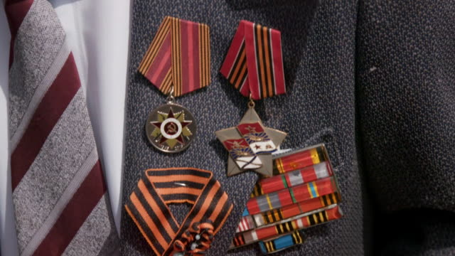 vídeos de stock e filmes b-roll de sequence showing the medals of an elderly wwii veteran (also wearing the ribbon of st george) who has received a bunch of flowers at an immortal regiment parade on wwii victory day in irkutsk, russia. - figura masculina
