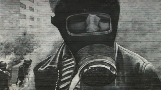 Sequence showing 'The Petrol Bomber' mural - a depiction of a boy in a gas mask at the Battle of the Bogside by the Bogside Artists at the People's Gallery in Londonderry/Derry, Northern Ireland.