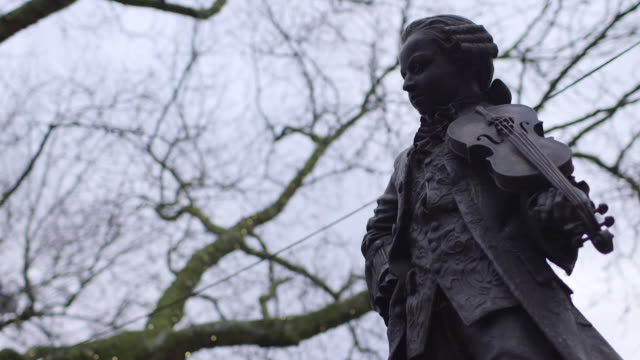 Sequence showing the statue of the young Wolfgang Amadeus Mozart against wintry bare trees in Orange Square in Belgravia, London.