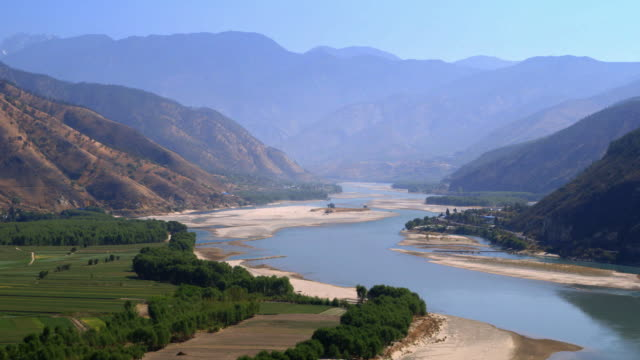 vídeos de stock, filmes e b-roll de sequence showing the yangtze river flowing through the countryside of the yunnan province in china. - yunnan province