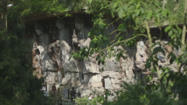 sequence showing tourists looking at three exquisitely carved figurines against a pattern of representations of buddha at the dazu rock carvings, chongqing municipality, sichuan province, china. - circa 5th century stock videos & royalty-free footage