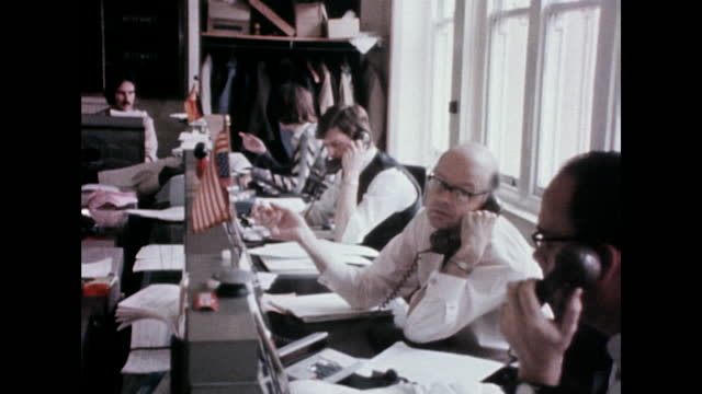 sequence showing traders talking on phones with old computer systems during trading in a busy foreign exchange market in london; 1975. - businesswear stock videos & royalty-free footage