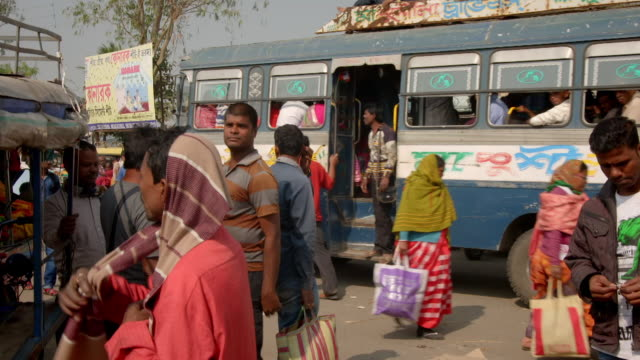 Sequence showing traffic and people changing buses in a small town in West Bengal, India.