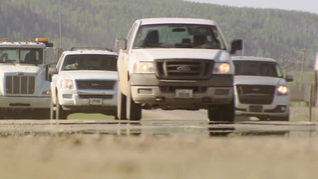 sequence showing traffic driving along highways near fort mcmurray in alberta, canada.  - trucks in a row stock videos & royalty-free footage