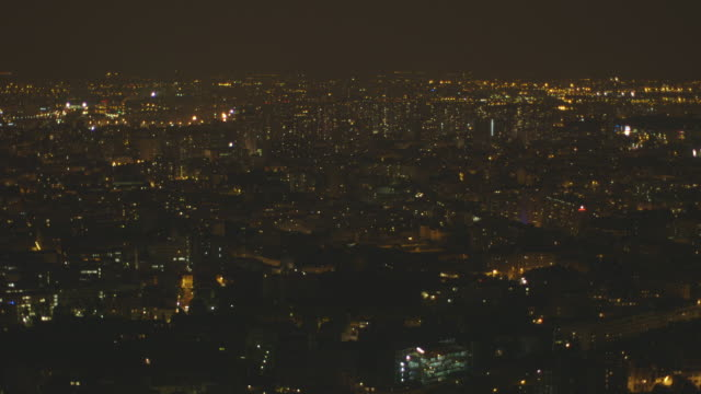 sequence showing two alternative tilts onto paris' vast skyline at night as seen from a high-rise building, france. - population explosion stock videos & royalty-free footage