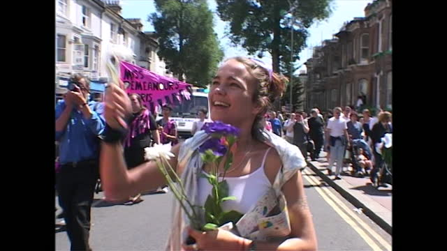 sequence showing two people in costume smiling and waving as they sit on a parade float and are handed a small bunch of flowers during a pride event... - sharing stock videos & royalty-free footage