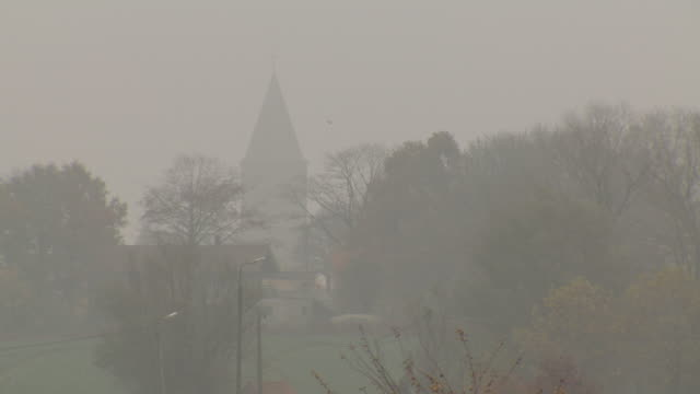 sequence showing two views of a church through fog, northern france. - bedeckter himmel stock-videos und b-roll-filmmaterial