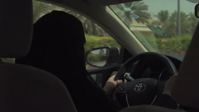 sequence showing two women in burkas driving in a car in riyadh soon after the driving ban for women is lifted - censura video stock e b–roll
