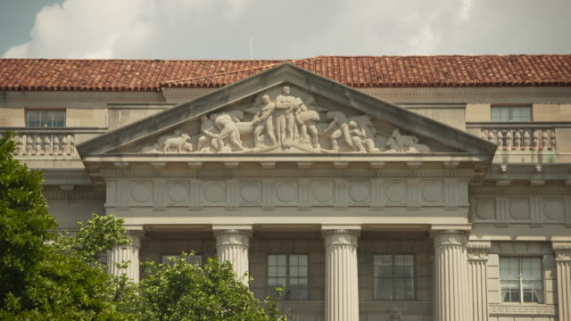 Sequence showing views of a frieze on a portico on the Herbert C. Hoover building in Washington, D.C., USA.