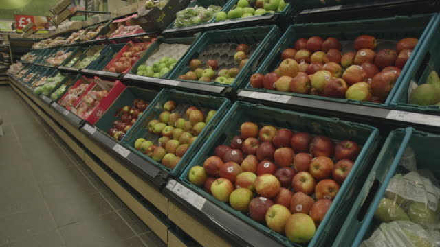 vídeos de stock e filmes b-roll de sequence showing views of apples on shelves in a uk supermarket. - vendas