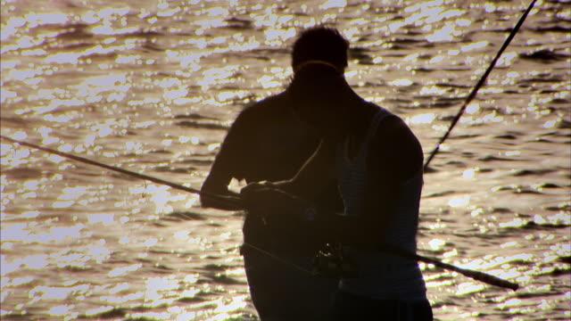 stockvideo's en b-roll-footage met sequence showing views of men fishing along havana's shoreline, cuba. - golf van mexico