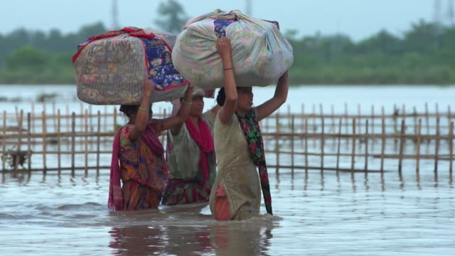 Sequence showing villagers wading through water in Assam in India during flooding