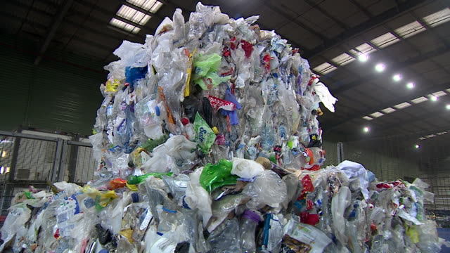 sequence showing waste at a uk recycling centre and a plastic milk bottle that can be made from recycled material in the form of pellets after news... - variation stock videos & royalty-free footage