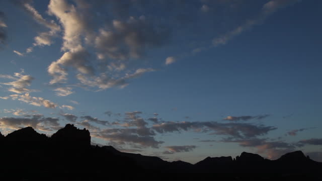 sequence showing wispy clouds moving across dramatic silhouetted rocks in arizona, usa. - wispy stock videos & royalty-free footage