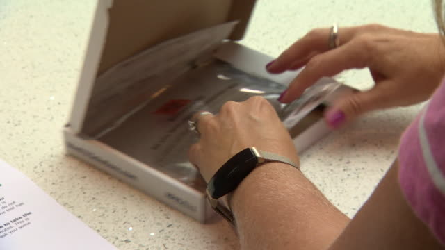 stockvideo's en b-roll-footage met sequence showing woman unpacking, using and returning a nhs coronavirus home test kit - opeenvolgende serie