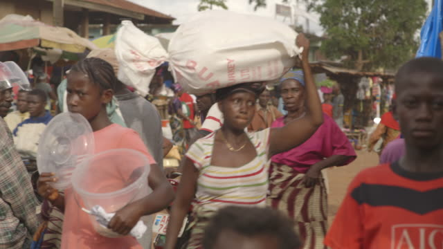 Sequence showing women carrying objects on their heads at a market in Sierra Leone.