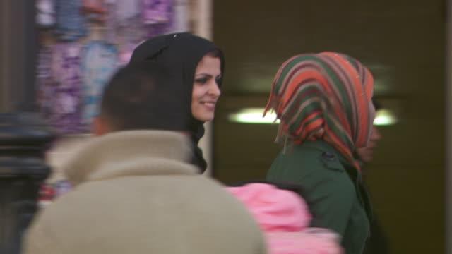 vídeos de stock, filmes e b-roll de sequence showing women some talking into mobile phones walking in ramallah in the west bank - ramallah