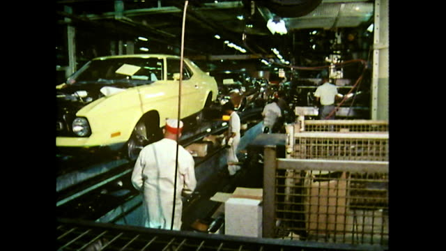 sequence showing workers on the ford river rouge plant production line assembling a yellow car as it moves past detroit 1972 - laboratory coat stock videos & royalty-free footage