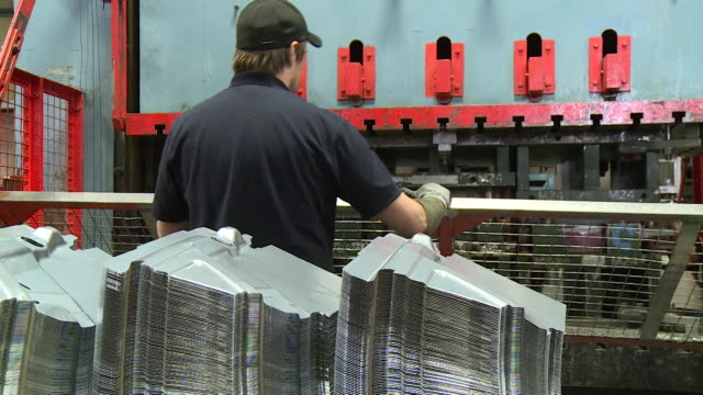 sequence showing workers operating a metal press in a factory - metal clip stock videos and b-roll footage