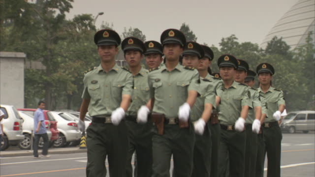 sequence showing young men wearing military uniform marching on a street in beijing, china. - military fitness stock videos and b-roll footage