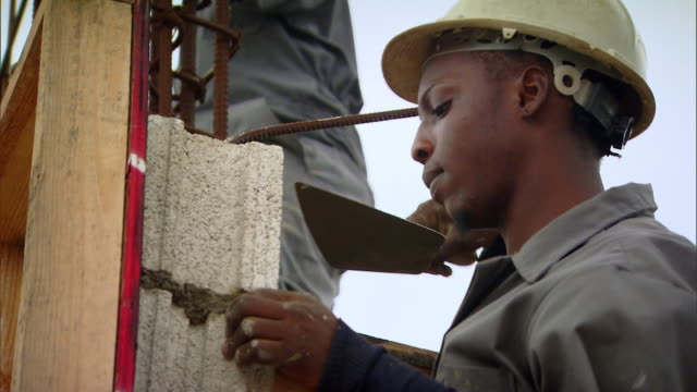 vidéos et rushes de sequence showing young people training on the job at a building site as part of jamaica's citizen security justice programme. - parpaing