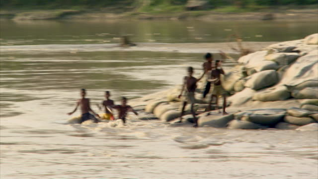 POV sequence taken from a boat showing children and a young man on the banks of the River Padma (known in India as the Ganges), Bangladesh.