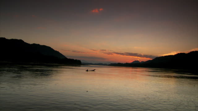 Sequence travelling along the Mekong River at dusk, Laos.