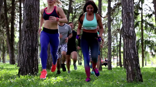 2 sequences - team of sport man and female running through trees in a park outdoors