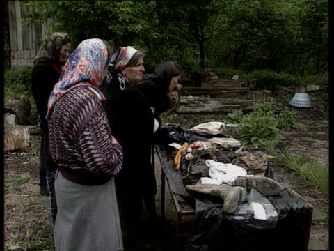 Serb massacre evidence BOSNIA HERZEGOVINA MS Press convoy of vehicles along road towards TRACK GV Wrecked buildings along road side TRACK Near...