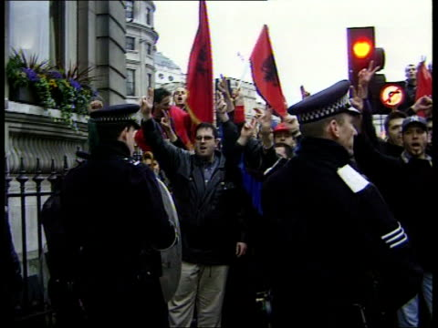 bombing continues: london demos; itn england: london: trafalgar square ext demonstrators supporting kosovo chanting as police guarding them kosovan... - serbia stock videos & royalty-free footage