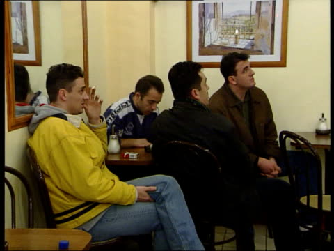 Kosovo NATO Bombing Continues/Refugee Crisis ITN ENGLAND London Abbey Road GV group of refugee Kosovo Albanian men standing in cafe watching Albanian...