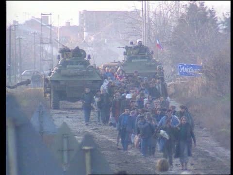 kosovo nato bombing continues/refugee crisis lib yugoslavia croatia vukovar tgv line of croatian refugees towards down road with tanks towards in b/g... - refugee stock videos & royalty-free footage