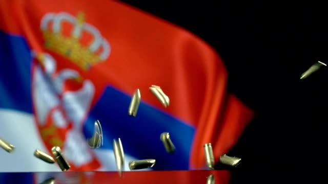 serbian flag behind bullets falling in slow motion - genocide stock videos & royalty-free footage