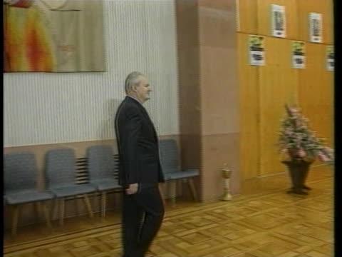 serbian president slobodan milosevic walks into a room and claps. - slobodan milosevic stock-videos und b-roll-filmmaterial