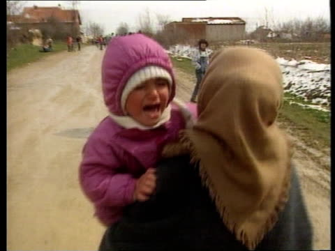 Serbian soldiers persecute Albanian refugees ITN Kosovo Glogovac Convoy of OSCE Monitor's orange jeeps towards past through snow as withdrawing LBV...