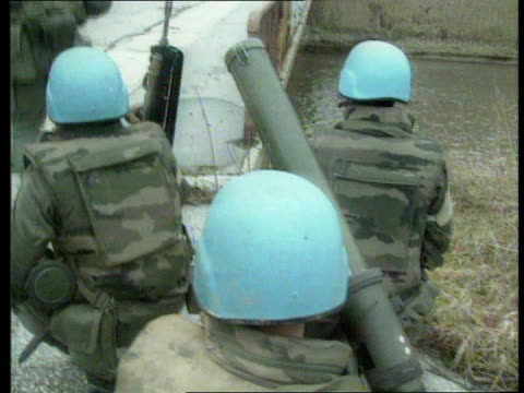 serbian/moslem agreement ext bv un soldiers along street track cms un soldier ms un soldier kneeling with rifle ms un soldier along past building... - セルビア点の映像素材/bロール