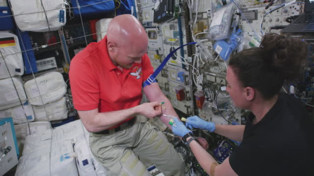 serena m auñónchancellor gets blood from astronaut alexander gerst the mission of expedition 56 began on 1 june 2018 upon the departure of soyuz ms07... - astronaut stock-videos und b-roll-filmmaterial