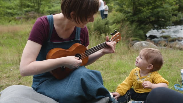 serenading baby with song on ukelele - musical instrument stock videos & royalty-free footage