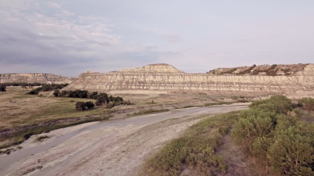 DRONE. Serene aerial view of small stream leading to prehistoric Badlands formations