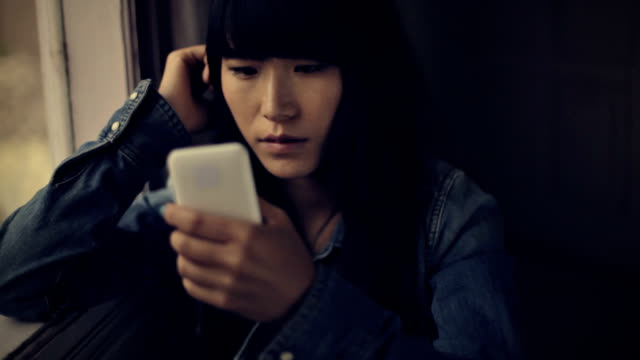 serene asian girl sitting near window and using phone. - blank expression stock videos & royalty-free footage