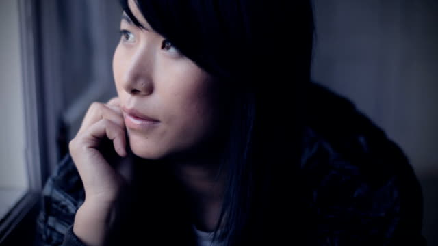 serene asian girl thinking while sitting near window. - looking away stock videos & royalty-free footage