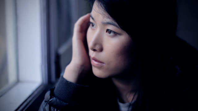 serene asian girl thinking while sitting near window. - tristezza video stock e b–roll