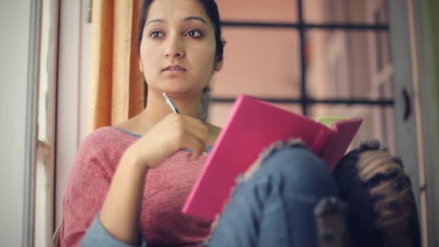 vidéos et rushes de serein asiatique jeune adulte étudiant près de la fenêtre avec le livre. - low angle view