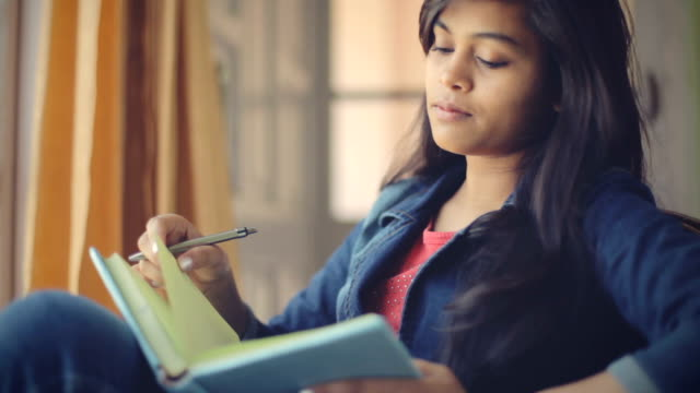 serene asian young adult student near window with book. - blocco per appunti video stock e b–roll