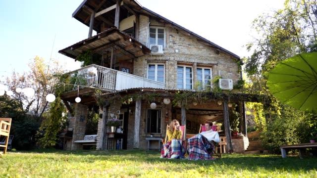 vídeos de stock e filmes b-roll de serene couple spending a relaxing day outdoors in a back yard drinking tea - apanhar sol