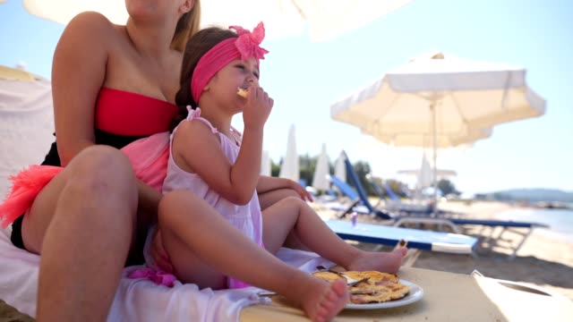 serene family of two eating breakfast on the beach - lounge chair stock videos & royalty-free footage